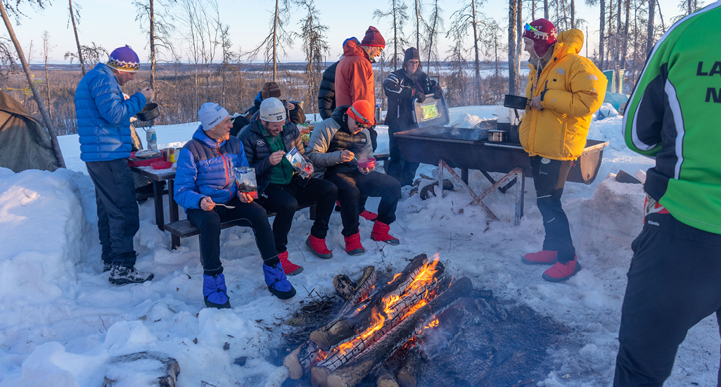 A group of tired skiers are gathered around a campfire as the sun goes down at the Don Allen Saskaloppet in La Ronge, Saskatchewan