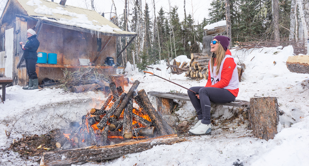 Ashlyn George is roasting a hot dog over an open fire at one of the rest stops during the Don Allen Saskaloppet in La Ronge Saskatchewan