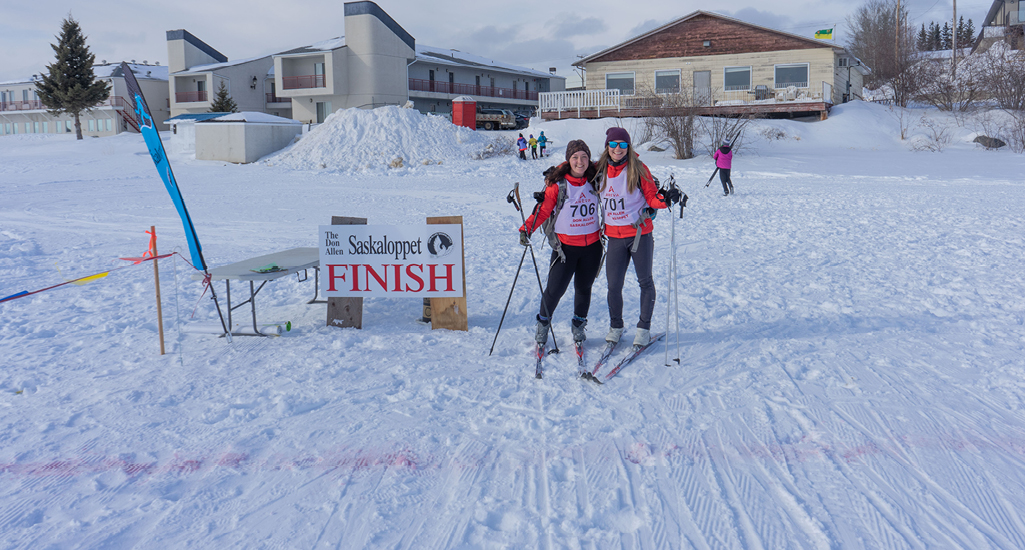 Two skiers celebrating at the finish line of the Don Allen Saskaloppet in La Ronge Saskatchewan