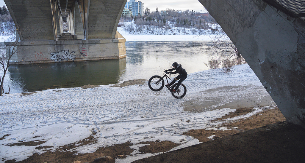 Winter biking under the Broadway Bridge along the shores of the South Saskatchewan River in the city of Saskatoon